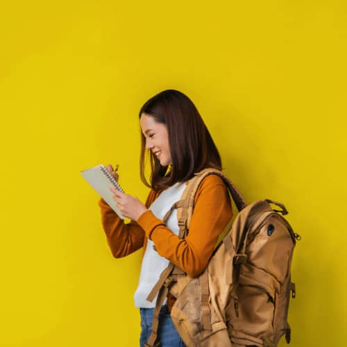 Female student in front of yellow backdrop